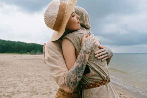 women hugging on beach